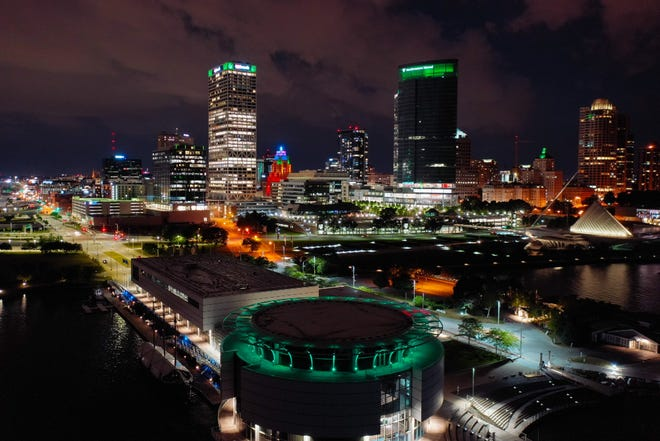 Milwaukee illuminated green overlooking Discovery World with the downtown skyline in the background