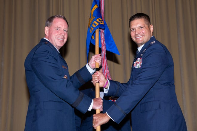 Lt. Gen. James Hecker, Commander and President Air University, passes the Guidon to incoming Commander Col. Lance Rosa-Miranda at the Squadron Officer School Assumption of Command Ceremony Maxwell AFB on June 21, 2021.