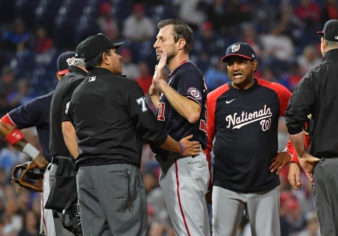 June 22, 2021; Philadelphia, Pa. -- Washington Nationals  pitcher Max Scherzer (31) and manager Dave Martinez (4) talk with umpire Alfonso Marquez (72) as they check for a foreign substance on Scherzer during the middle of the fourth inning against the Philadelphia Phillies at Citizens Bank Park.