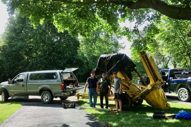 Grateful gentlemen Tom McGlynn and Jim Ackron talk with Westchester Village resident Shawn Burkett who came to their rescue when they needed help after a major mechanical problem on the tree-planting trailer. They were grateful for his kindness.