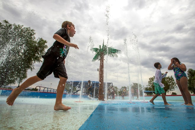 Children play in the water feature at La Quinta Park in La Quinta, Calif., on June 23, 2021.