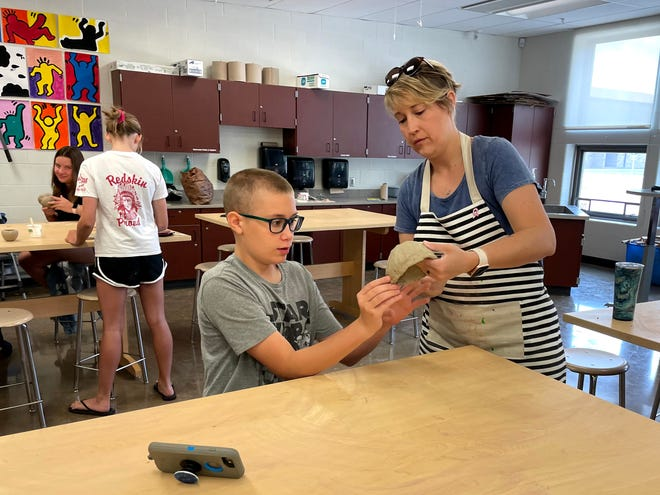 Keegan Lukac works with art teacher Jen Davis on a pottery project during Art Camp at Port Clinton Middle School.
