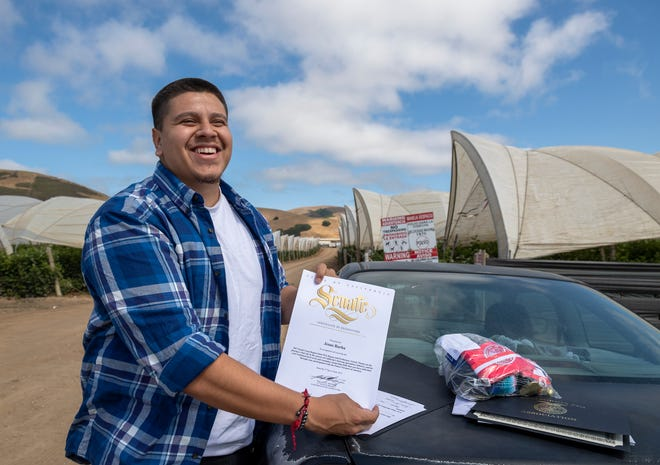 Jesus Adrian Barba smiles as he holds one of his many Future Farmers of America (FFA) awards that he received in high school in Salinas, Calif., on Monday June 21, 2021.