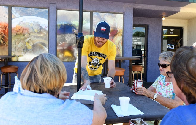 Matt Beukelman hands food orders to lunch customers on Wednesday, June 23, 2021, at Watecha Bowl in Sioux Falls.
