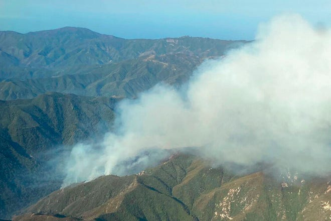 In this photo provided by the California Interagency Willow Fire Incident, smoke rises from the Willow Fire near Big Sur, Calif., on Sunday, June 20, 2021. Dozens of wildfires were burning in hot, dry conditions across the U.S. West. In California, firefighters still faced the difficult task of trying to contain a large forest fire in rugged coastal mountains south of Big Sur that forced the evacuation of a Buddhist monastery and nearby campground. (California Interagency Willow Fire Incident via AP)