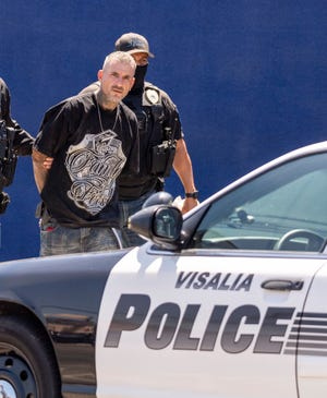 Visalia Police take a man into custody in the 500 block of North Willis Street on Wednesday, June 23, 2021. A suspect fleeing from police and parole officers eventually surrendered after darting between the rooftops of a house and Glicks & Co. Butcher Shop.