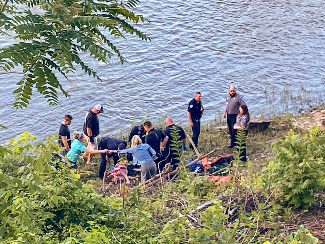Emergency personnel attend to a teenager after she was pulled from the Muskingum River by a young man dining outside at Muddy Misers Tuesday evening.