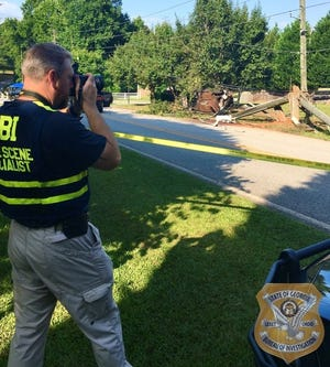 A Georgia Bureau of Investigation agent photographs the scene of a fatal shooting Thursday in Barrow County.