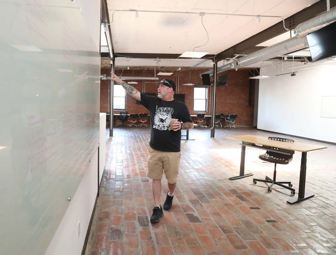 Tugg Massa of Akron Say No to Dope points to client goals listed on a board on June 24 as he stands inside a downtown space that will become an addiction treatment facility called Akron House Recovery.