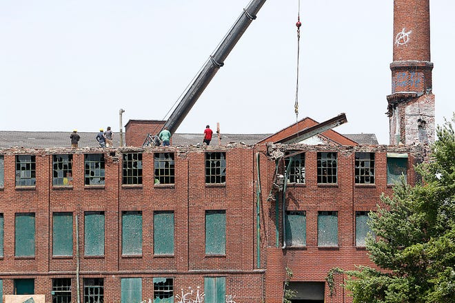 A beam is removed from the old Hess & Clark plant as demolition crews continue the demolition of the building on Thursday, June 24, 2021. TOM E. PUSKAR/TIMES-GAZETTE.COM