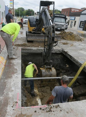 City employees and contractors try to fix the broken water main on Kellogg Avenue Thursday, June 24, 2021, in Ames, Iowa.