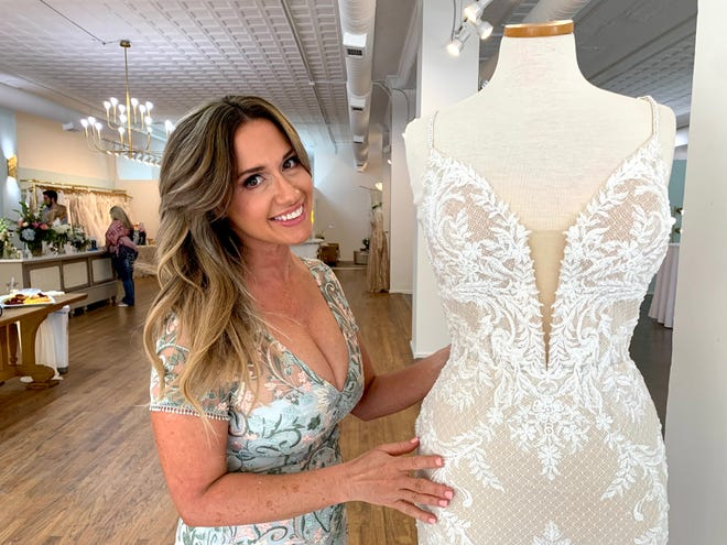 Brandy Gibson admires one of the dresses on display at the new location of her store, Tiffinie Bleu Bridal Boutique, on Broad Street.
