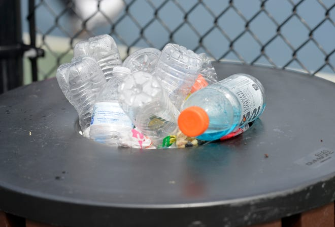 Plastic bottles overflow from a trash can at pickleball courts in Mashpee.