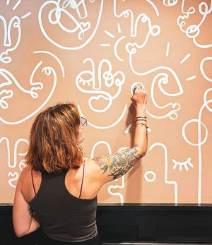 Adrienne Luther works on the walls of Hoot Design Company