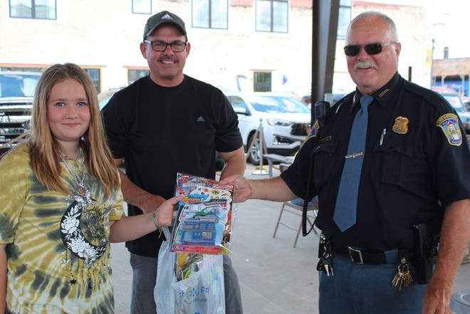 At the Cheboygan Department of Public Safety Community Appreciation Picnic on Wednesday, 12-year-old Marley Dunn (left) presented Sgt. Ron White (middle) and Chief Kurt Jones (right) with bags of books and toys to be given out to children when the officers respond to situations in the community.