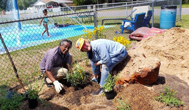 Crestview Citizen of the Year Felton Barnes, and Dr. Cathy Ward, founder of the Common Ground Community Garden, plant flowers in a community garden being established near Fairview Center in Allen Park, located on McClelland Street in Crestview.
