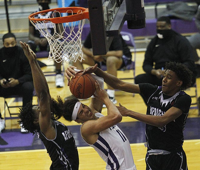 Africentric's Elijahjuan Burke, left, and Dailyn Swain fight Pickerington Central's Garner Wallace for the ball during their game at Pickerington on Saturday January 30.