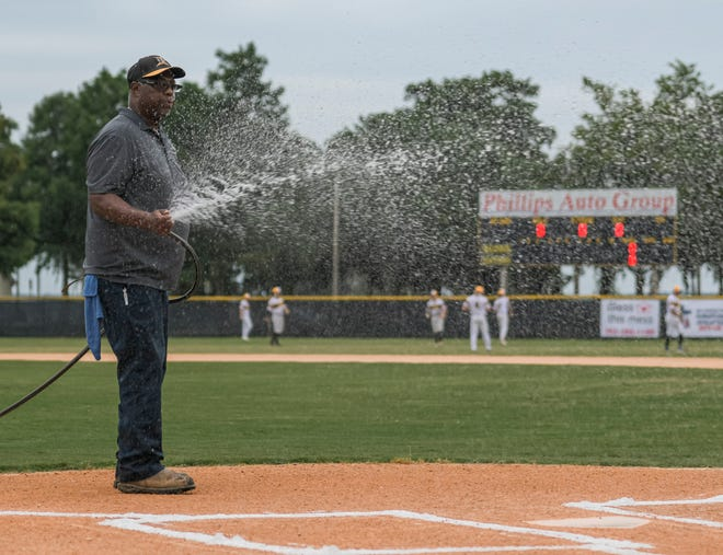 Michael Thompson wets the dirt around home plate before a recent Leesburg Lightning game at Pat Thomas Stadium-Buddy Lowe Field. Thompson has been the Lightning's one-man graounds crew since the team's inception in 2007. [PAUL RYAN / CORRESPONDENT]