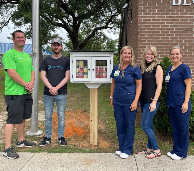 Standing by the Little Food Pantry at the Freeport Public Library are (from left) Brian Lundblom and Jesse Senn from Publix; Melissa Beadle, care management coordinator at Ascension Sacred Heart Emerald Coast; Walton County Public Library System Director Director Caitlin Cerise; and Linsey Hall, care coordinator for Ascension Sacred Heart and MyGulfCare.