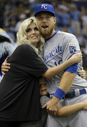 Kansas City Royals' Ben Zobrist, right, hugs his wife Julianna during a video tribute before a baseball game against the Tampa Bay Rays, Friday, Aug. 28, 2015, in St. Petersburg, Fla. Zobrist played nine season for the Rays. Holding on to Zobrist is his son Zion. (AP Photo/Chris O'Meara)