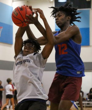 """Bartow's Jaiden Wynn and Winter Haven's Jadarius """"JD"""" Cobb fight for a rebound during action in the championship game of the 2021 Polk County Summer League."""