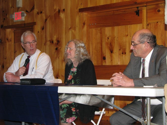 Sen. Charles Trump (left) speaks to the crowd while fellow legislators Del. Ruth Rowan and Sen. Randy Smith listen at the Mineral County Chamber of Commerce Members Meeting and Legislative Update.