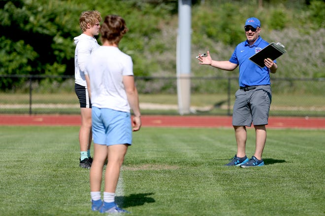 Winnacunnet High School head football coach Ryan Francoeur speaks to his team at the start of  Wednesday's 7-on-7 passing session with York High School in Hampton.