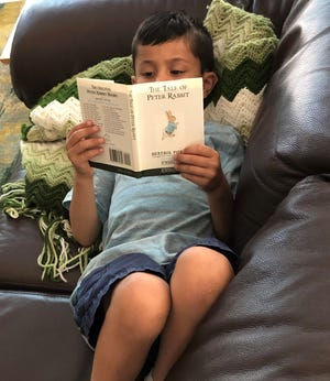 """Kathy Grant's grandson Sam enjoying """"The Tale of Peter Rabbit"""" on a hot afternoon."""