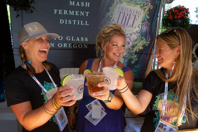 Kerry Weeks, left, Emily Jensen and Alicia Hayden from Thinking Tree Spirts in Eugene serve up cocktails during the Olympic Track and Field Trials from Agate Street in the shadow of Hayward Field.