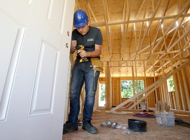 Jake Wessel,17, a student at Early College High School, installs a door knob on a Habitat for Humanity house in Canton.