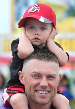 Jack Gordon covers his ears to block the sounds of the rides while sitting on the shoulders of his father Derek Gordon during the Jackson Community Festival on Wednesday.