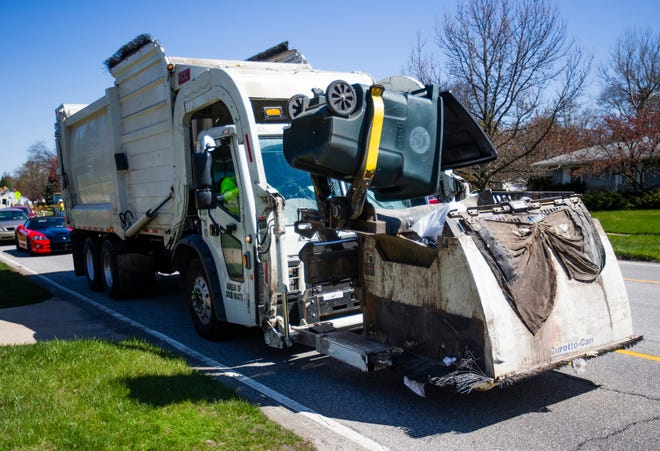 A city of South Bend trash truck empties a container on Ironwood Drive in April 2020 during the height of the COVID-19 pandemic. City households, staying home from work and school, generated 14% more trash during the pandemic, exacerbating pre-existing annual deficits in the city's solid waste program. A new bill would increase rates to help balance the department's annual budgets.