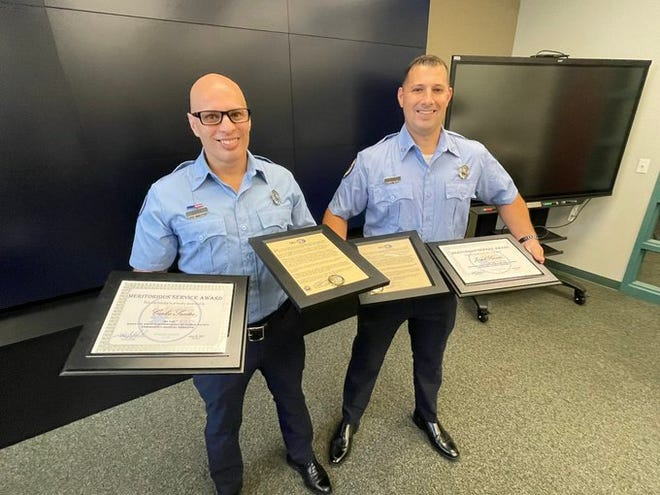 Manatee County paramedics Carlos Santos (left) and Joe Savasta received the Manatee County Meritorious Service Award and the County Administrators ACE Challenge Coin Award for deescalating a dangerous situation while responding to a call.
