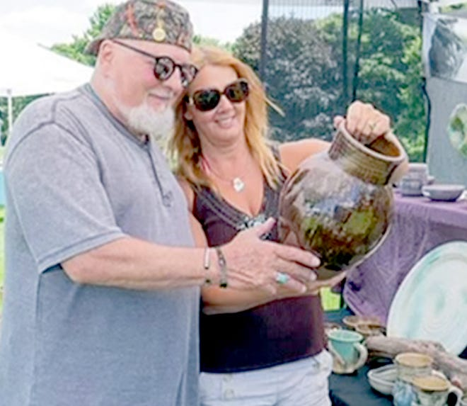 """Shireen Cline, organizer of """"Art on the Green,"""" looks at an item with a vendor at a previous event.  """"Art on the Green"""" for 2021 is June 26 at Island Hills Golf Club."""