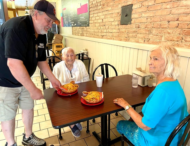 Eta Settle and Marlene Boyer are served taco salads at Mike's Pizza on one of their recent trips.The pair are glad to be back out dining again and say they feel safe.