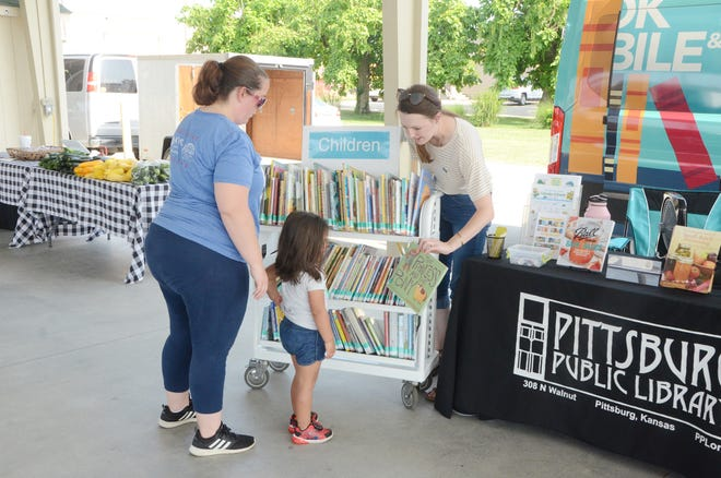 Public Service Librarian Jessica Ziesenis shows a book to Elena Herrera at the Pittsburg Area Farmers' Market on Wednesday.