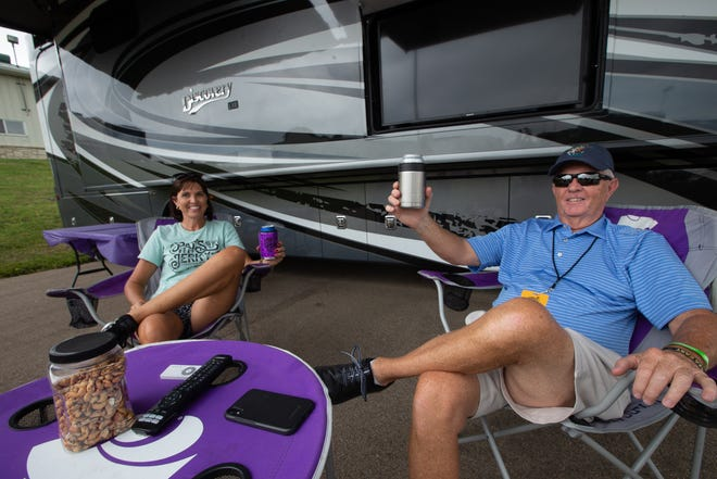 Van Witthuhn and his daughter Renae Willey enjoy a cold beer outside their motorhome Thursday at Heartland Motorsports Park for the Country Stampede. The family has traveled to the Stampede for more than 10 years.