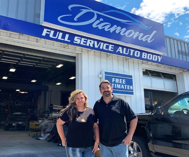 Juan and Tanara Tolomio in front of their auto shop in Worcester.