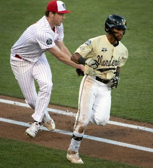 NC State pitcher Sam HIghfill (17) tags out Vanderbilt left fielder Javier Vaz (2) as he tries to get to first base on a bunt during game six in the NCAA Men's College World Series at TD Ameritrade Park Monday, June 21, 2021 in Omaha, Neb.  Nas Vandy Nc State 036