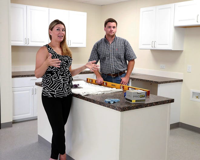 Ashley Forsgren, Fort Smith Children's Shelter director of development, left, and Jack Gray, life coach, talk about the community commitment to the shelter, during a tour, Thursday, June 24, of the new Life Skills Activity Center on the shelter campus.