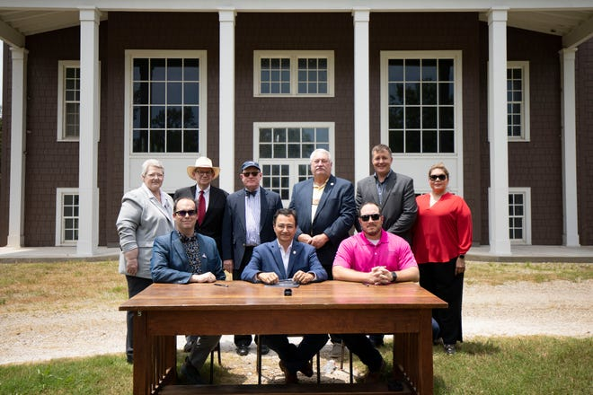 Cherokee Nation officials joined representatives from Dwight Presbyterian Mission to formalize the acquisition of the historic Sequoyah County property. Officials are photographed in front of the 1917 schoolhouse, which was renovated in 2014 with vital support from Cherokee Nation. Front row: Preston Bobo, board vice president for Dwight Presbyterian Mission Inc., Cherokee Nation Principal Chief Chuck Hoskin Jr., and Deputy Principal Chief Bryan Warner. Back row: Secretary of State Tina Glory Jordan, Bill Wiles, board treasurer for Dwight Presbyterian Mission Inc., Charlie Smith, administrative officer for Indian Nations Presbytery, District 5 Tribal Councilor E.O. Smith, Chief of Staff Todd Enlow, and Cherokee Nation Delegate to Congress Kimberly Teehee.