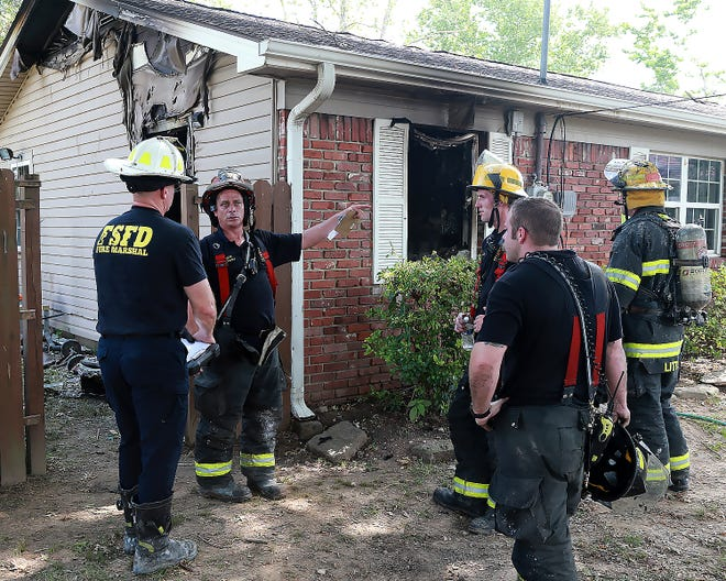 Fort Smith Fire Department Fire Marshal, Ethan Millard, left, talks with Fort Smith Fire Department Station 3 Captain, Arlen Gourley, after a house fire, Thursday, June 24, in the 2500 block of Brockman Avenue.
