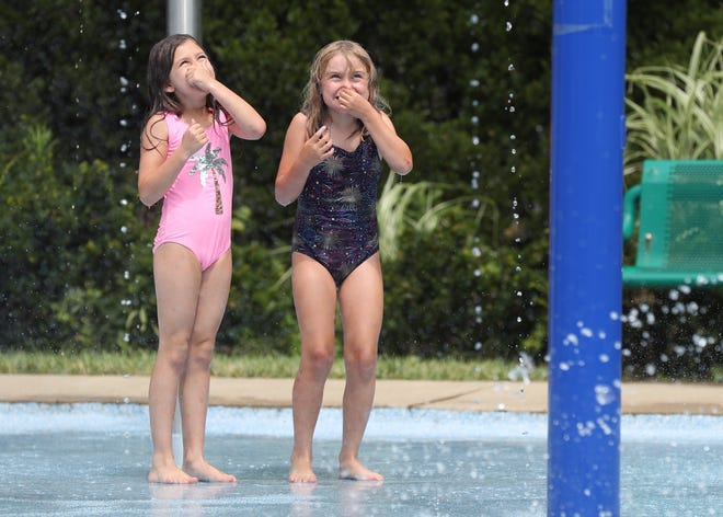 Sofia Garcia Guerra (left), 6, of Powell and Rosalind Kauffman-Itani, 7, of Clintonville hold their noses as they eagerly wait for a bucket of water to spill over them June 23 at the splash pad at Village Green Park, 47 Hall St. in Powell. The splash pad was closed until June 9 while repairs were made.