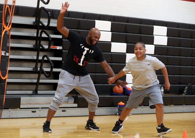 Shawn Jeter, Whitehall-Yearling High School varsity boys basketball assistant coach, guards Keishawn Foster, 13, of Whitehall during a summer sports camp June 23 at the high school.