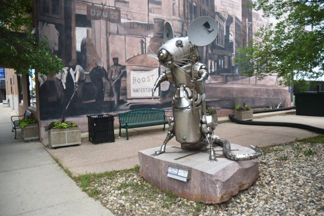"""Disney and Pixar's icon Ratatouille stands erect on Kemp Avenue in a statue created by Minnesota artist Dale Lewis. According to a plaque on the base of the sculpture it was inspired by the Direct TV satellite dishes the artist  wanted to use for ears. """"Most of the found objects used are stainless steel kitchenware. I also used a sink from my cousin's dairy farm and my friend's gas grill top. The large whisk was saved for several years waiting for the right sculpture. The kinky whiskers were salvaged from a heavy woven screen. Ratatouille is meant to be fun, not a statement about any restaurant that may choose to display him,"""" the plaque reads. This sculpture is one of 16  featured on the 2021 Watertown Artwalk organized by the Watertown Area Community Foundation."""