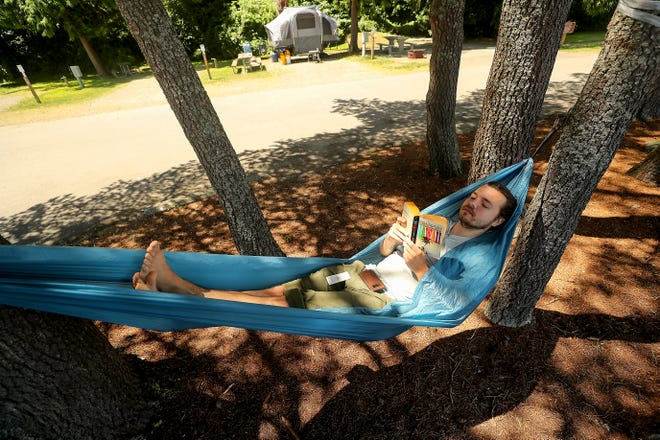Alec Stenerson relaxes in his hammock strung between the trees at Bainbridge Island's Fay Bainbridge Park on Thursday, June 24, 2021. Stenerson, an Ohio native, was camping at the park while on a cross country trip.