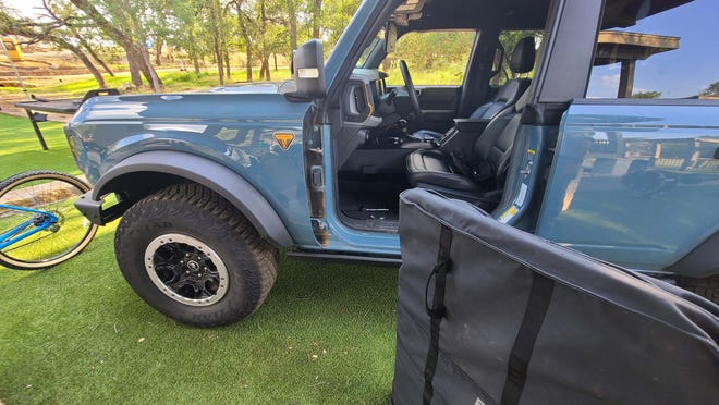 It's never easy to remove 50-pound doors, but the 2021 Ford Bronco helps with an efficient removal process that includes three bolts, a electronic harness plug, LIFT hand slot, and door bags.