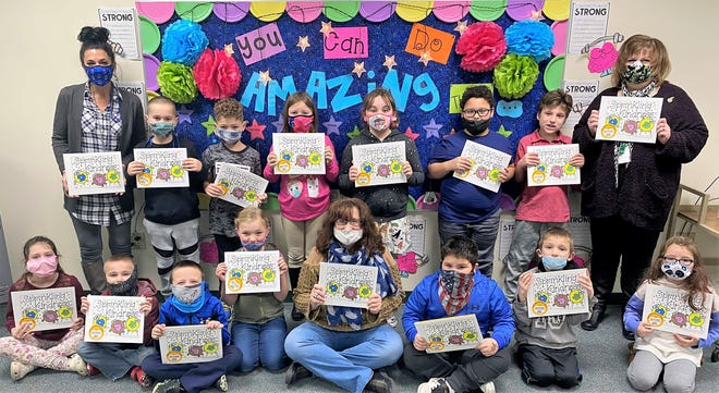 Caroline Laurin-Young's second-grade class at Oconto Elementary School hold their copies of Sprinkling Kindness books, which they researched, wrote and illustrated. From left, front row: Olivia Daul, Matthew Steele, Connor Carriveau, Annabelle Klein, Mrs. Caroline Laurin-Young, Dominick Diaz, Connor Gilligan, Sloan Belongia ; back row:  Paraprofessional Carroll Stellmacher, Brady Thomson, Jeffery Skarban, Remmee Stellmacher, Maggie Resch, Javon Reed, Lucas Edgar, Special Education teacher Sheryl Hendricks.