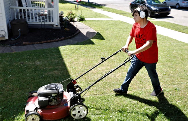 Cameron Petro-Roy, 13, mows a lawn on Allen Street Tuesday, June 22. The Lancaster teen is participating in the Raising Men Lawn Care Service program, which is dedicated to servicing lawns of military veterans, elderly residents or anyone that needs assistance.