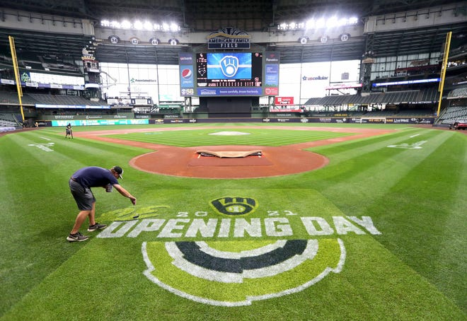Milwaukee Brewers groundskeeper Zack Peterson works on painting a new logo on the field marking Re-Opening Day 2021 at American Family Field in Milwaukee on Thursday, June 24, 2021. The Brewers take on the Colorado Rockies in a3:10p.m. start Friday that combines that first thrill of a normal opening day in springtime, with the reality that for the first time since 2019 the Brewers can play a game at full attendance. - Photo by Mike De Sisti / Milwaukee Journal Sentinel via USA TODAY NETWORK